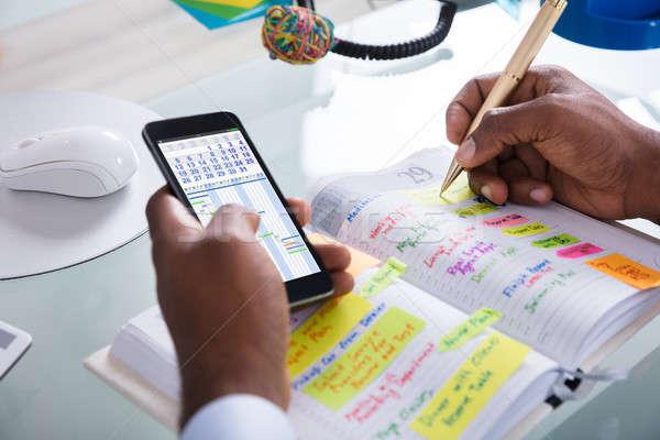 üzletember tart mobiltelefon ír menetrend napló Stock fotó © AndreyPopov