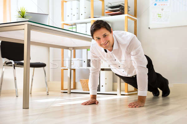 Stock photo: Businessman doing push up