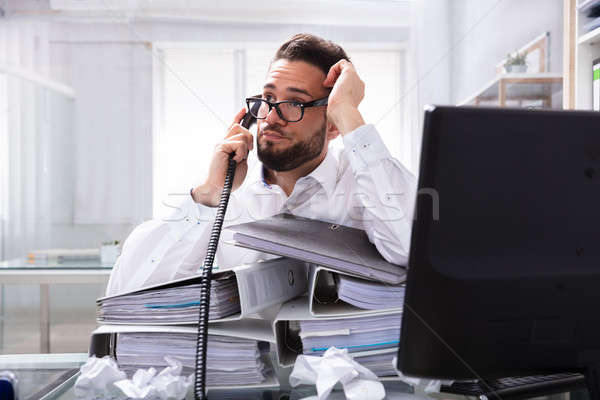 Overworked Businessman Talking On Landline Stock photo © AndreyPopov