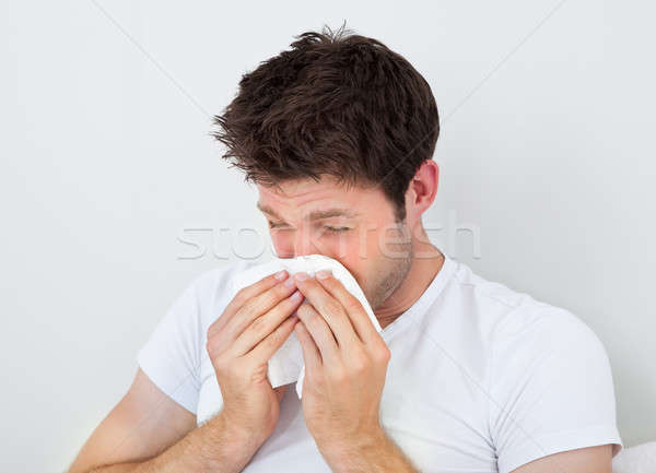 Man Sneezing Into A Tissue Stock photo © AndreyPopov