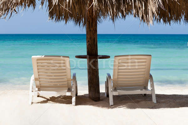 Lounge Chairs Under Sunshade At Beach Stock photo © AndreyPopov