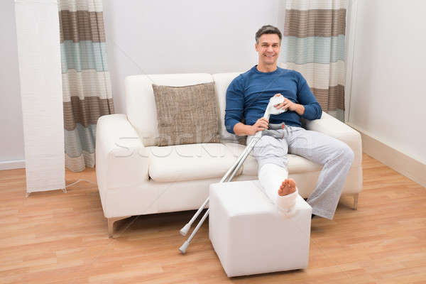 Man Sitting On Sofa With Crutches Stock photo © AndreyPopov