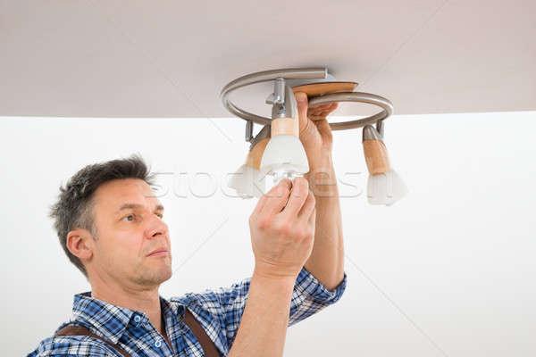 Technician Fixing Light On Ceiling Stock photo © AndreyPopov