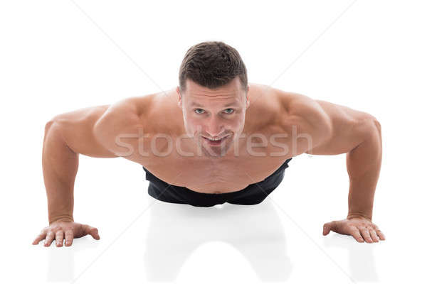 Stock photo: Determined Muscular Man Doing Push Ups