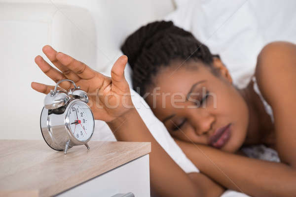 Woman Turning Off Alarm While Sleeping On Bed Stock photo © AndreyPopov