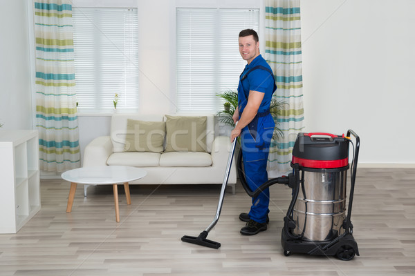 Worker Cleaning Floor With Vacuum Cleaner At Home Stock photo © AndreyPopov