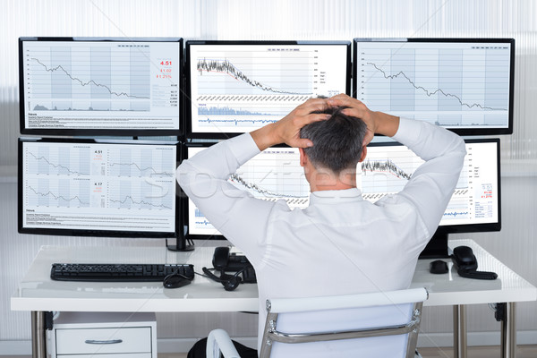 Trader With Hands On Head Looking At Graphs On Screens Stock photo © AndreyPopov