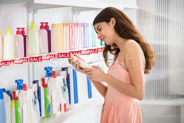 Női vásárló kiválaszt kozmetikai üveg polc Stock fotó © AndreyPopov