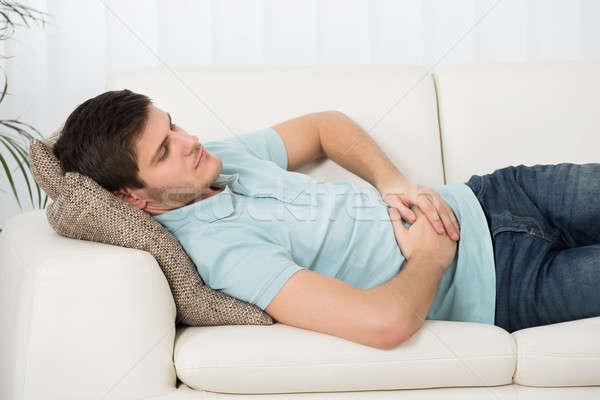 Férfi szenvedés gyomorfájás otthon kanapé személy Stock fotó © AndreyPopov