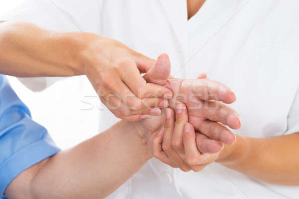 Person Receiving Palm Massage By Physiotherapist Stock photo © AndreyPopov