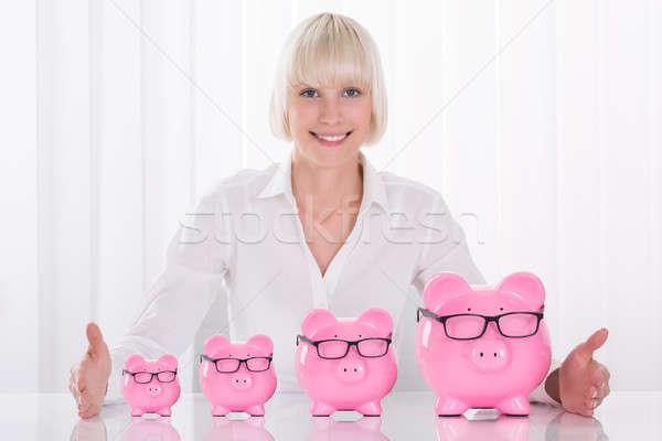 Businesswoman Hand Protecting Piggybanks On Desk Stock photo © AndreyPopov