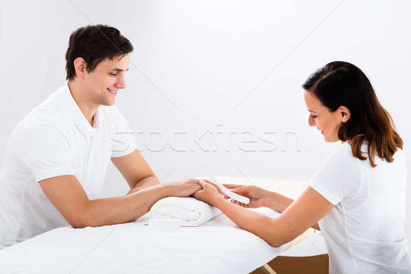 Manicurist Filing Man's Nails In Salon Stock photo © AndreyPopov