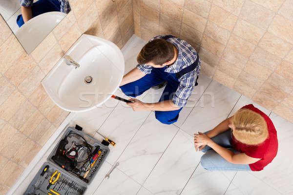 Young Male Plumber Fixing Sink In Bathroom Stock photo © AndreyPopov