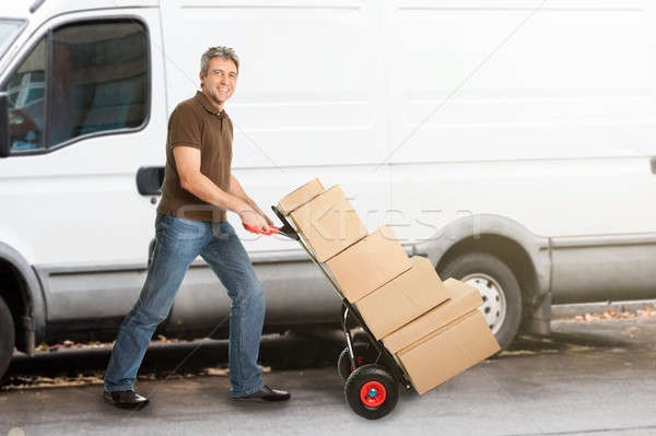 Delivery Man Pushing Parcels On Handtruck Stock photo © AndreyPopov