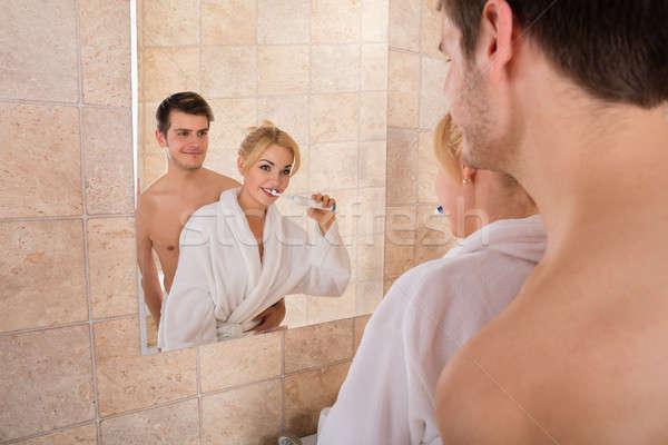 Stock photo: Young Couple Brushing Teeth In Bathroom