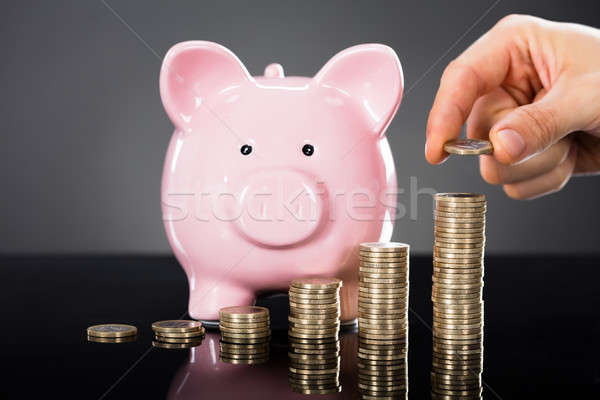 Person Stacking Coins In Front Of Piggybank Stock photo © AndreyPopov