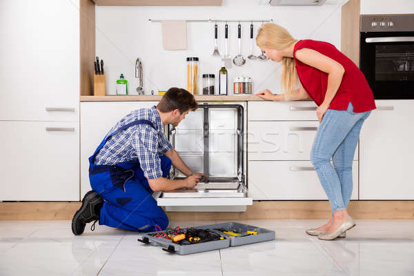 Woman Looking At Repairman Repairing Dishwasher Stock photo © AndreyPopov