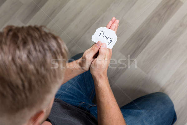 Piece Of Paper With Text Pray In Man's Hand Stock photo © AndreyPopov