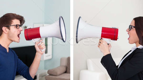 Man And Businesswoman Screaming Into Megaphones Stock photo © AndreyPopov