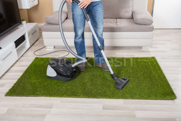 Person Cleaning Green Carpet With Vacuum Cleaner Stock photo © AndreyPopov