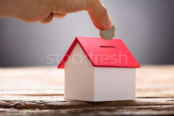 Hand Putting Coin In House Piggy Bank Stock photo © AndreyPopov