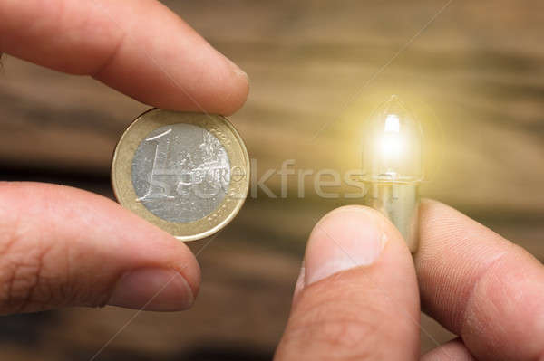Hands Holding One Euro Coin And Lit Lightbulb Stock photo © AndreyPopov
