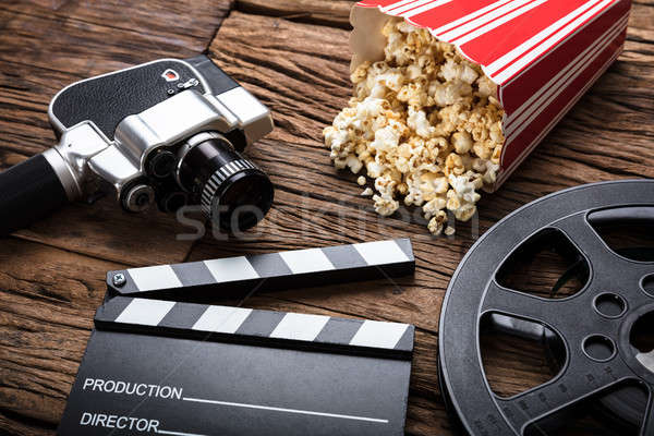 Movie Camera With Clapper Board And Popcorn On Wood Stock photo © AndreyPopov