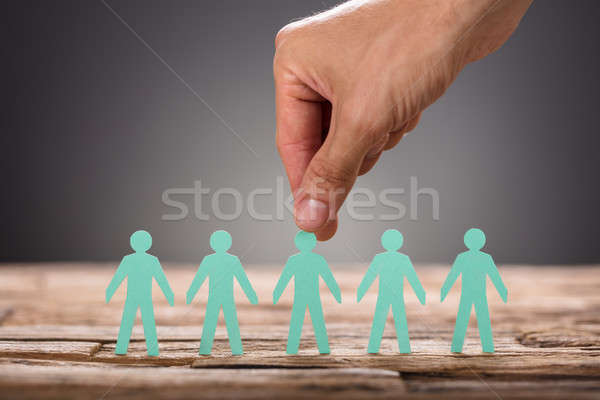 Hand Picking Green Paper Man Representing Recruitment Stock photo © AndreyPopov