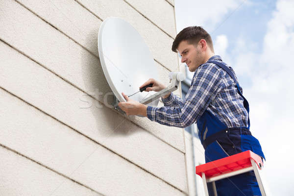Technician Installing TV Satellite Dish On Wall Stock photo © AndreyPopov
