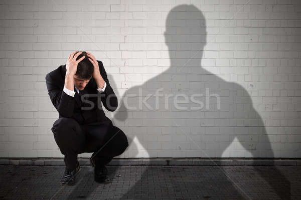 Businessman Getting Scared From The Shadow Falling On Wall Stock photo © AndreyPopov