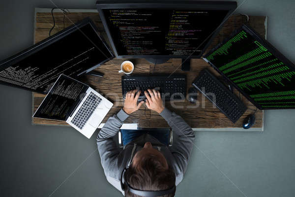 Hacker Hacking Multiple Computers On Desk Stock photo © AndreyPopov
