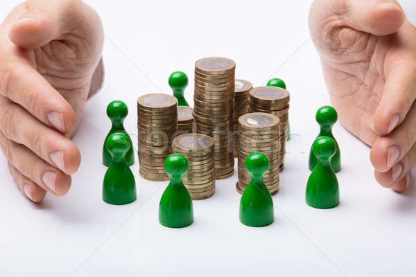 Hands Protecting Coin Stack Surrounded With Green Figures Stock photo © AndreyPopov