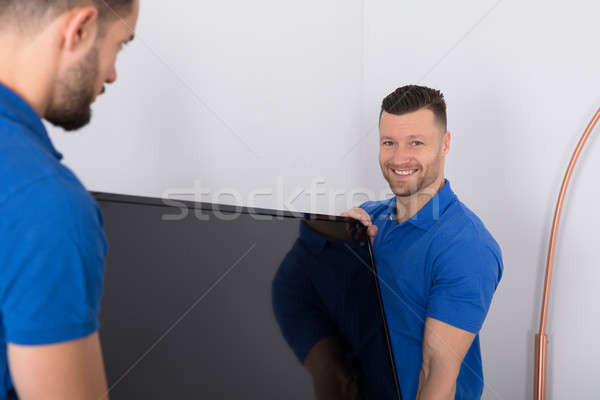 Two Movers Placing Television In Living Room Stock photo © AndreyPopov