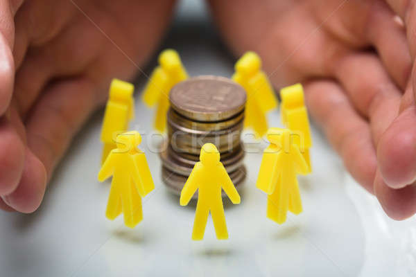 Businessperson Protecting Stacked Coins And Yellow Human Figures Stock photo © AndreyPopov