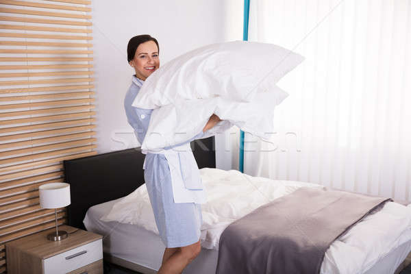 Female Housekeeper Carrying Pillows In Hotel Room Stock photo © AndreyPopov