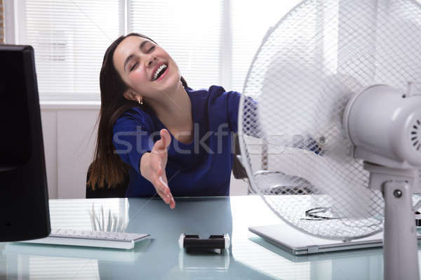 Businesswoman Sitting On Chair Cooling Herself With Electric Fan Stock photo © AndreyPopov