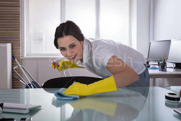 Happy Female Janitor Cleaning Desk With Rag Stock photo © AndreyPopov