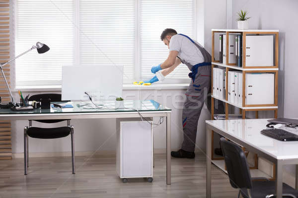 Janitor Cleaning The Window Sill In Office Stock photo © AndreyPopov