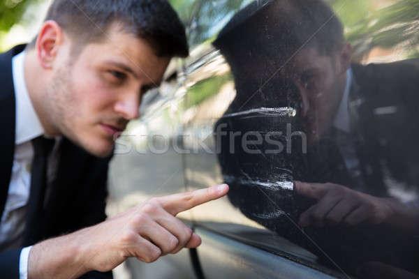 Stock photo: Man Inspecting Damaged Car