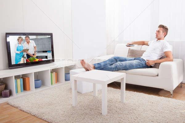 Fiatalember tv nézés ül kanapé néz film Stock fotó © AndreyPopov