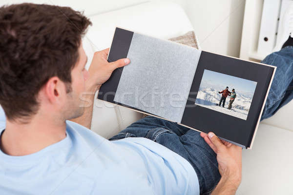 Young Man Looking At Photo Album Stock photo © AndreyPopov