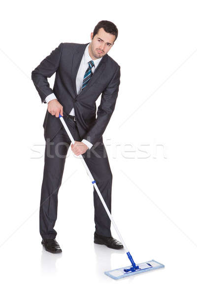 Businessman cleaning floor Stock photo © AndreyPopov