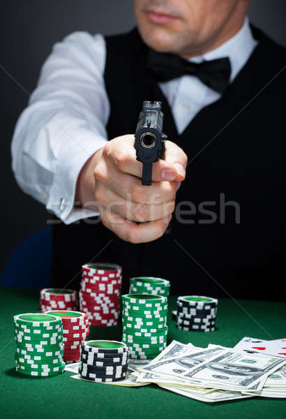 Portrait of a croupier aiming with a gun Stock photo © AndreyPopov