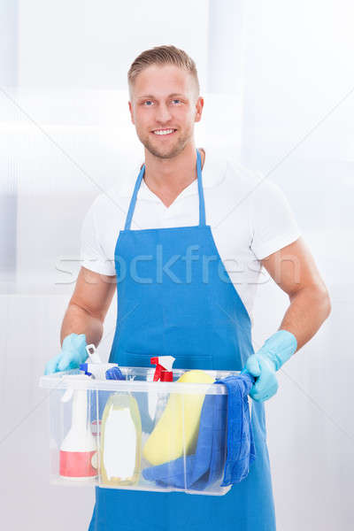 Happy janitor with a tub of cleaning supplies Stock photo © AndreyPopov