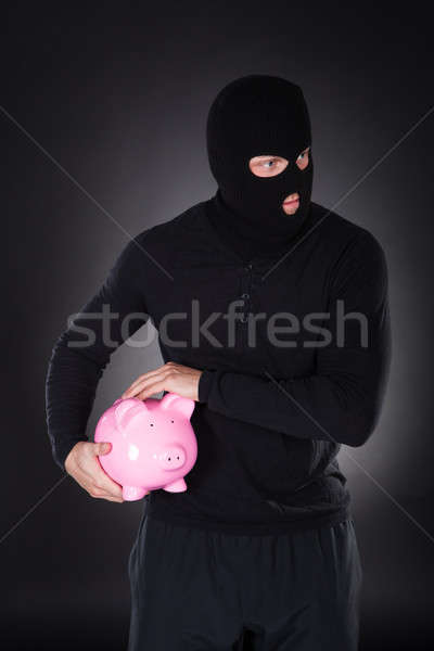 Burglar stealing a pink piggy bank Stock photo © AndreyPopov