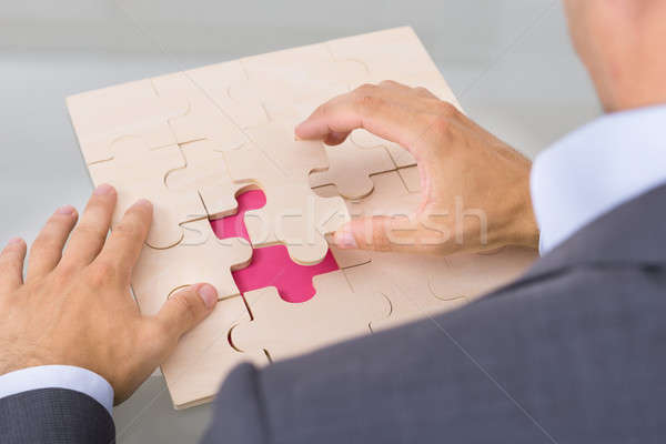 Businessman assembling jigsaw puzzle Stock photo © AndreyPopov