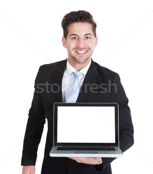 Confident Businessman Displaying Laptop Over White Background Stock photo © AndreyPopov