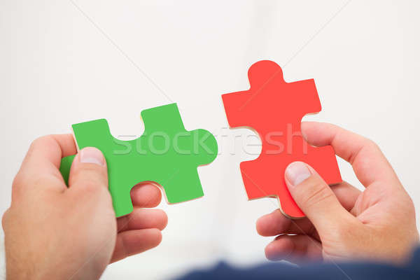 Man Joining Puzzle Pieces Stock photo © AndreyPopov