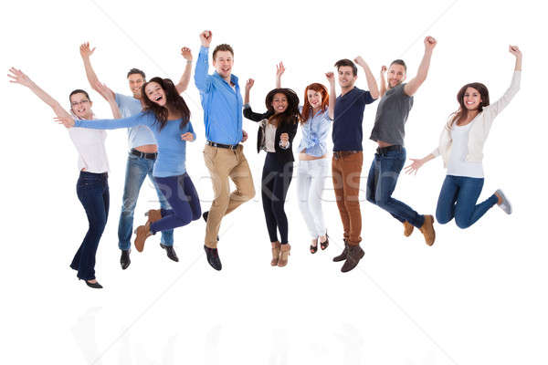 Group of diverse people raising arms and jumping Stock photo © AndreyPopov