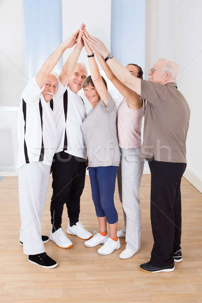Stock photo: People Joining Hands Together At Gym
